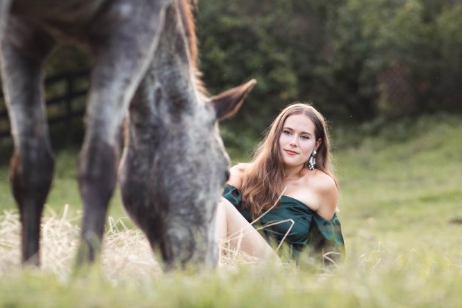 girl lying in grass next to horse